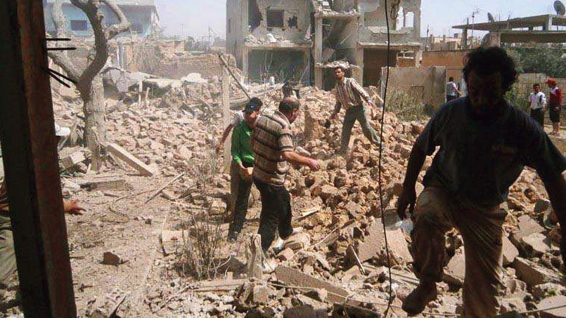 Des Syriens inspectaient, samedi à al-Qusayr, les ruines d'un immeuble détruit par des attaques aériennes du régime.