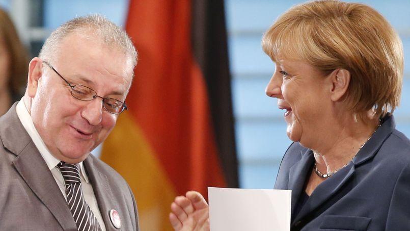 Angela Merkel en discussion avec le représentant de la communauté turque d'Allemagne, Kenan Kolat, lors de l'ouverture du sommet pour l'intégration, mardi à Berlin.