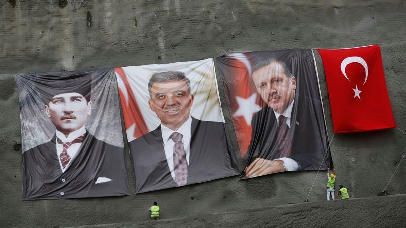 Des ouvriers installent des portraits d'Abdullah Gül (au centre) et de Recep Tayyip Erdogan (à droite) à côté de celui d'Atatürk, fondateur de la Turquie moderne, et du drapeau national.