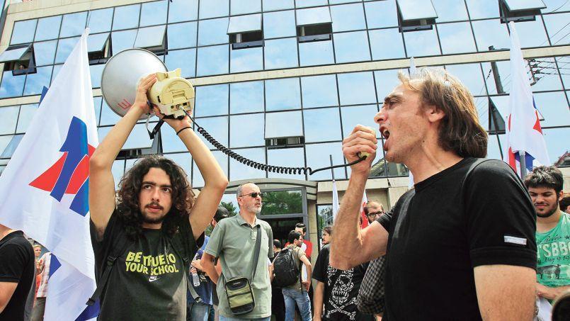 Syndicalistes et salariés des chaînes publiques grecques ERT manifestent devant le siège de la télévision mercredi à Athènes. Toutes les émissions des trois chaînes nationales d'ERT ont été arrêtées mardi soir.