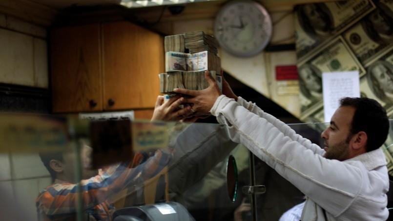 L'Égypte n'effectue aucun contrôle systématique de ses comptes publics et les rares audits pratiqués demeurent secrets d'État (photo d'illustration, deux hommes dans un bureau de change, au Caire).