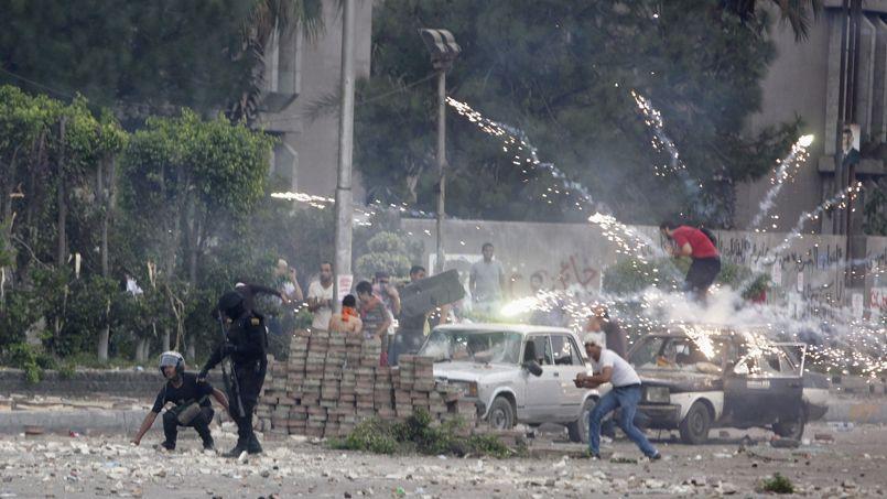 Des supporteurs de Mohammed Morsi attaquent des voitures de police à coups de feu d'artifice, lors des violents affrontements de samedi à Nasr City dans l'est de la capitale, Le Caire.