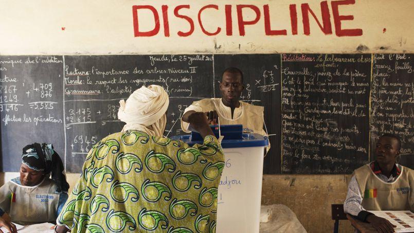 Une femme dépose son bulletin, dimanche, lors du premier tour de la présidentielle dans un bureau de Tombouctou.