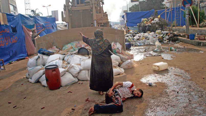 Au Caire, une femme s'interpose entre un bulldozer de l'armée et un jeune homme blessé au cours des affrontements sanglants, mercredi, dans le camp de la place Rabaa al-Adawiya.