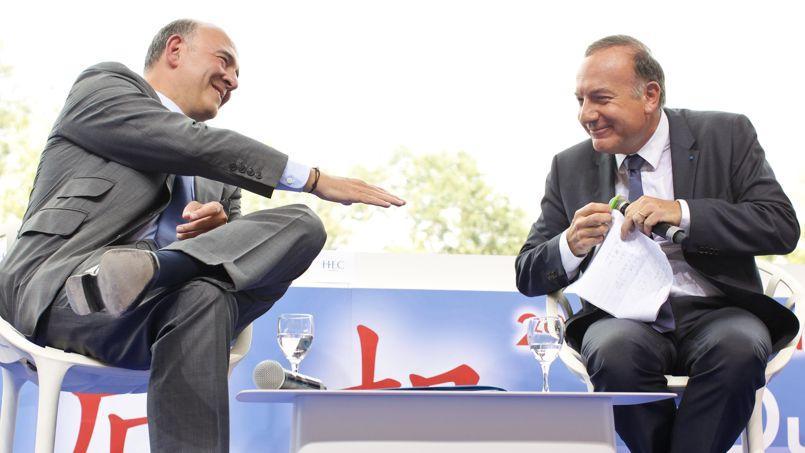 Poignée de mainentre le ministre des Finances, Pierre Moscovici, et le président du Medef, Pierre Gattaz, jeudi, à Jouy-en-Josas.