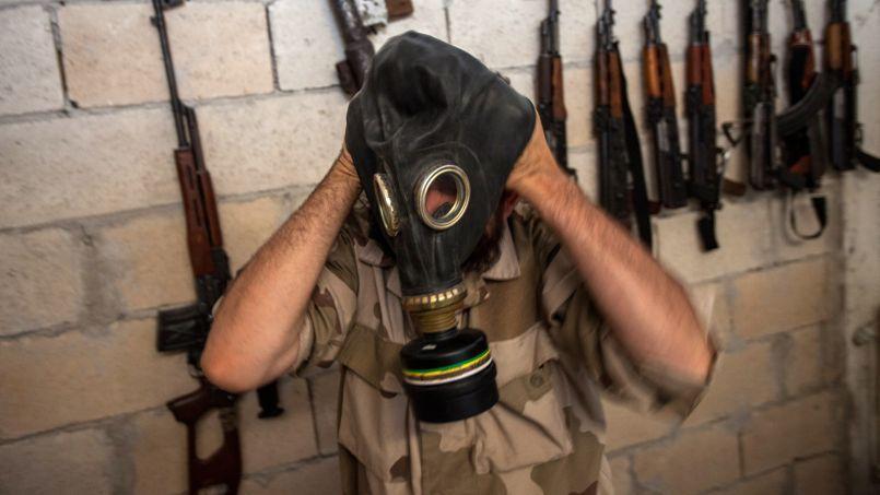 Un soldat rebelle syrien essaye un masque à gaz, en juillet, dans la province d'Idlib.