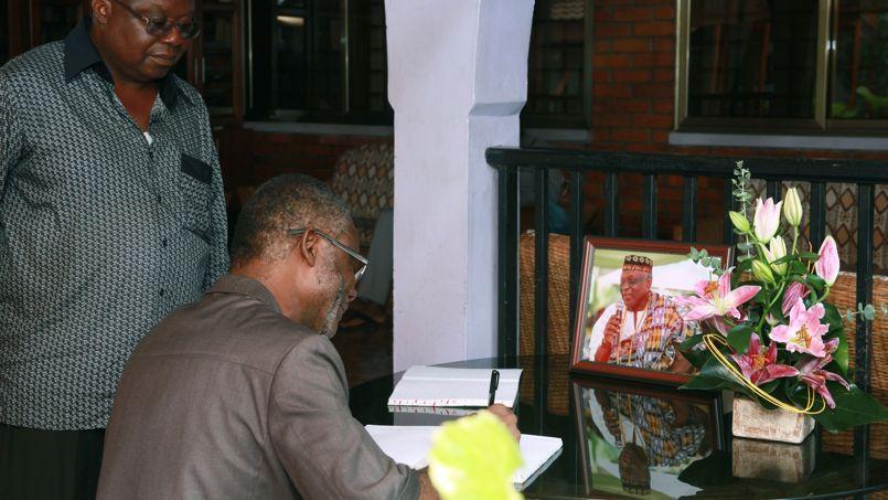 John Henry Martey Newman, directeur de cabinet du président ghanéen, signe le livre de condoléances dédié au poète Kofi Awoonor, visible dans le cadre à droite.