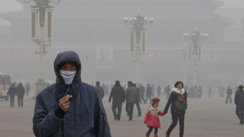 Des touristes dans le brouillard place Tiananmen, à Pékin.