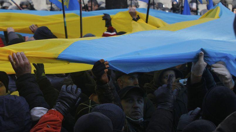 Les manifestants ont déployé un énorme drapeau ukrainien pendant l'occupation de la place devant le Parlement à Kiev mardi.