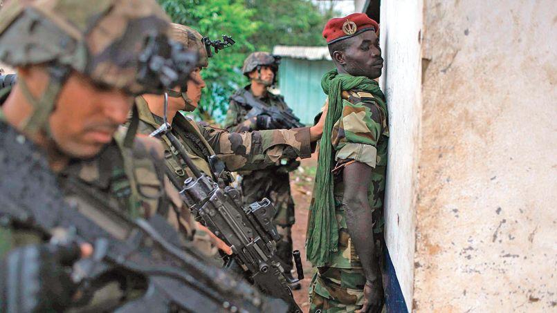 Des soldats français contrôlent un officier de l'ex-Séléka à Bangui, lundi.