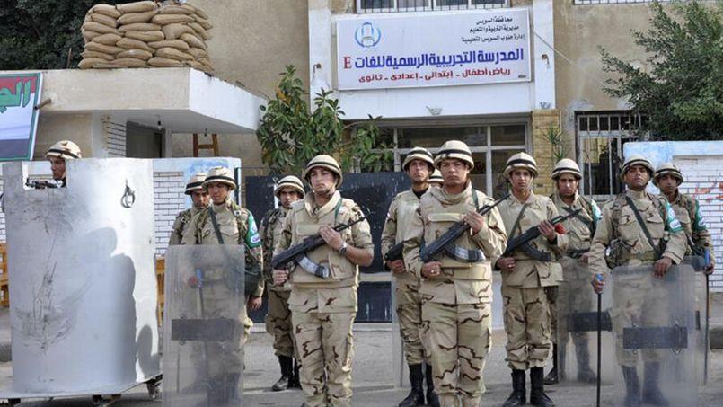 Des soldats égyptiens devant un bureau de vote à Suez, lundi.