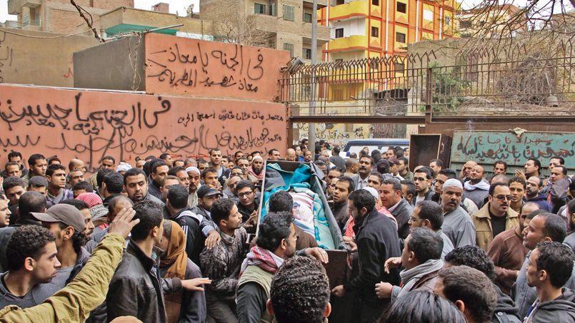 À la morgue de Zeinhom au Caire, des Égyptiens portent le cercueil d'un homme tué samedi lors des affrontements avec les forces de l'ordre.