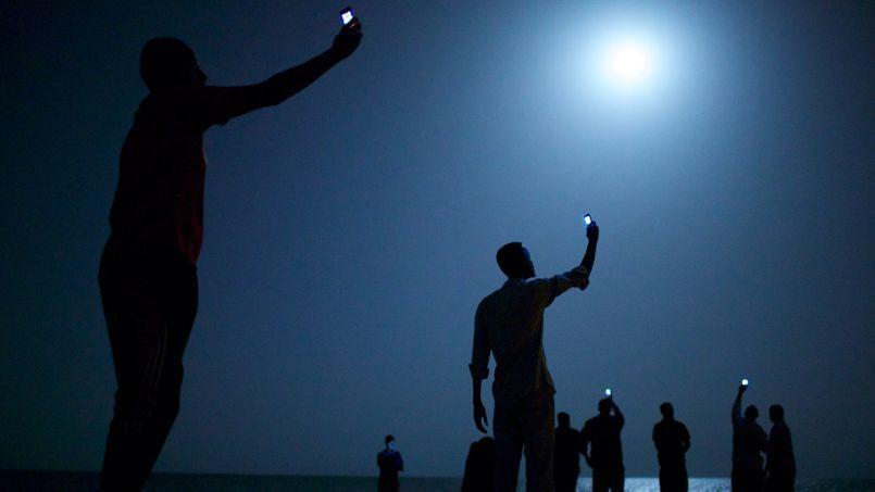 Photo de John Stanmeyer. Des migrants africains orientent leur téléphone vers le ciel pour obtenir du réseau.