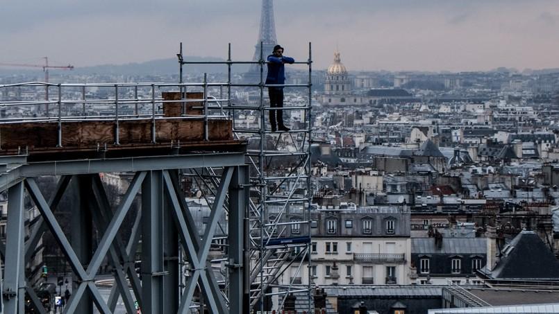 L'artiste JR sur un échafaudage, à Paris. Une bâche protégera la coupole du Panthéon. Elle sera constellée de milliers de portraits d'anonymes, pris par JR dans un camion Photomaton.
