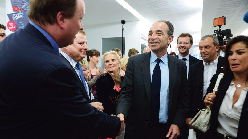 Jean-François Copé, accompagné de son épouse, Nadia, et son directeur de cabinet, Jérôme Lavrilleux, est applaudi à son arrivée au siège de l'UMP, lundi à Paris.