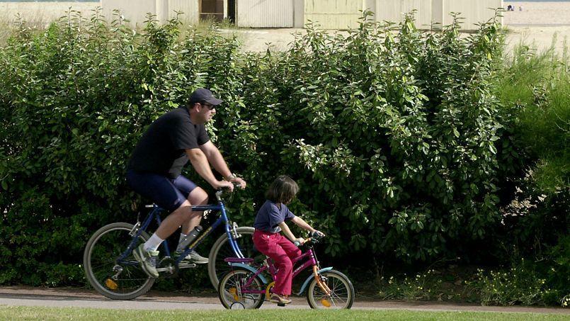 Un père et sa fille se promènent à vélo, le long de la plage de Ouistreham (Calvados).