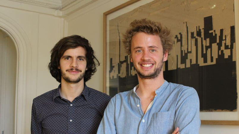 Les cofondateurs François-Xavier Trancart et Hugo Mulliez posent devant une des oeuvres proposées à la vente sur Artsper.com.