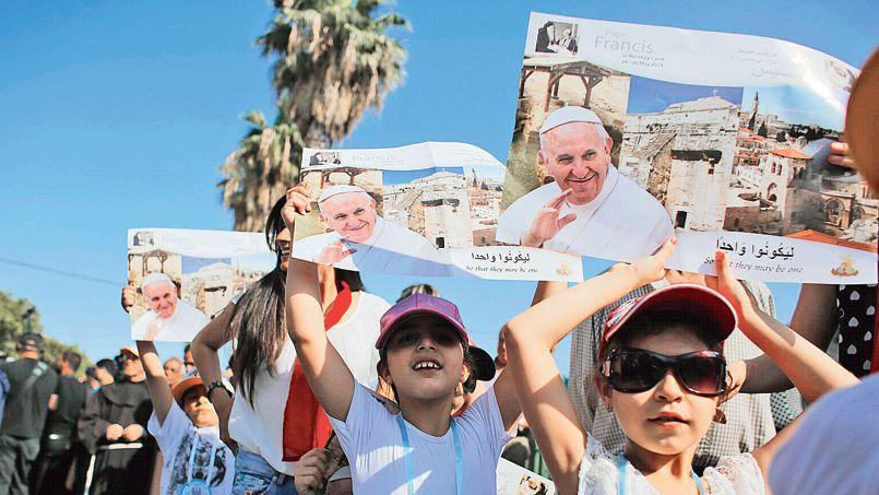 Des enfants brandissent des affiches annonçant la future visite du pape François lors d'une procession, dimanche, à Haïfa.