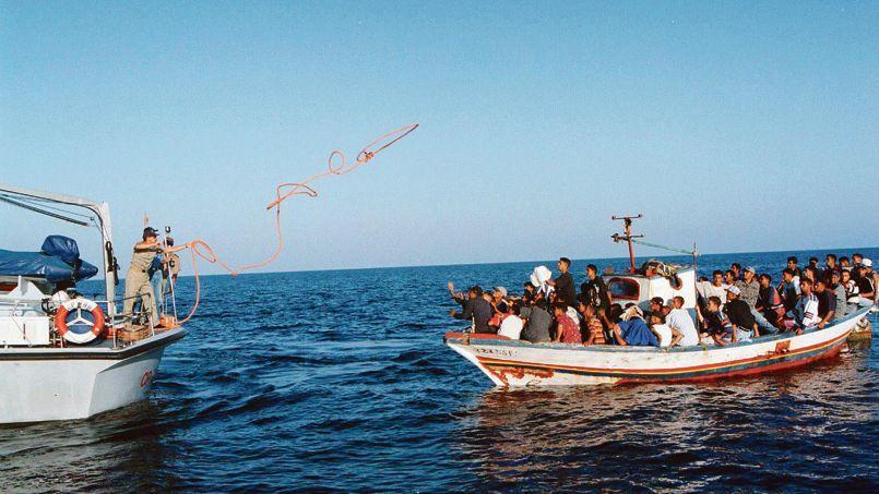 Bateau de réfugiés recevant l'aide de la marine italienne au large de l'île de Lampedusa.