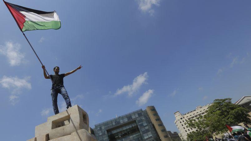Un manifestant brandit un drapeau palestinien devant un bâtiment des Nations Unies à Beyrouth, le 24 juillet.