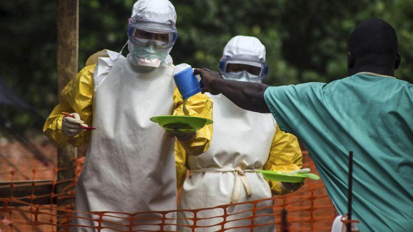 Le personnel médical travaillant avec Médecins Sans Frontières se préparent à apporter de la nourriture aux patients en isolement dans un centre de traitement, à Sierra Leone.