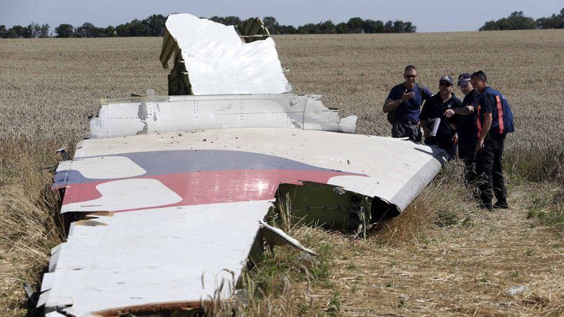 Des experts australiens et néerlandais examinent, vendredi, des pièces du fuselage du MH17 sur le site du crash, à proximité du village de Hrabove dans l'est de l'Ukraine.