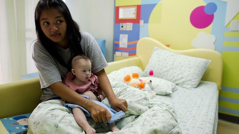 Une mère porteuse thaïlandaise tient son bébé, né avec le syndrome de Down, et abandonné par ses parents biologiques, un couple d'Australiens.