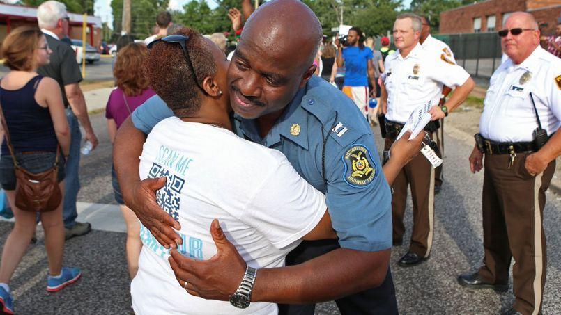 Le capitaine Ron Johnson prend dans ses bras Angela Whitman, une manifestante pendant la manifestation pacifique de jeudi soir à Ferguson, théâtre de violentes émeutes depuis la mort brutal d'un jeune Afro-américain le week-end dernier.