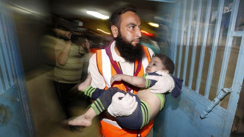 Un médecin palestinien transporte un enfant blessé par le raid israélien sur Gaza, mardi.