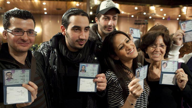 Des immigrants français montrent leur nouvelle carte d'identité israélienne lors d'une cérémonie organisée par l'Agence juive à Jérusalem en décembre 2009.