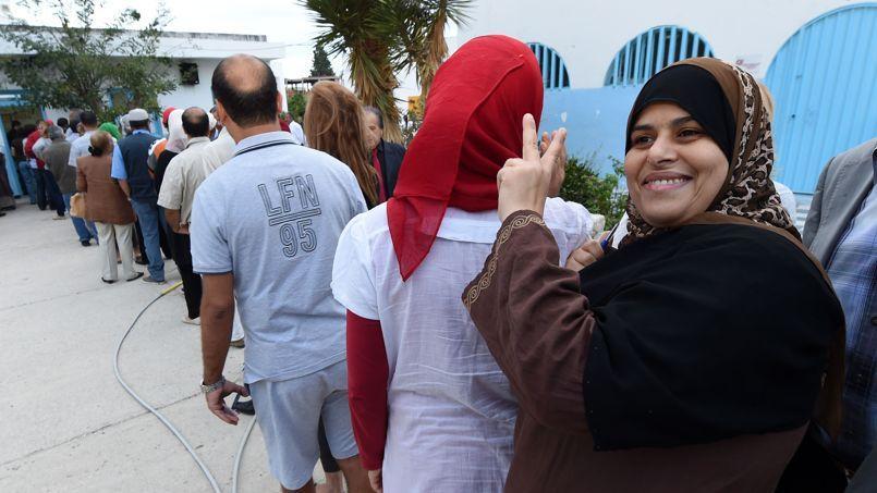 Les files d'électeurs se sont très tôt formées dans les 33 circonscriptions devant désigner à la proportionnelle 217 députés parmi quelque 1300 listes de candidats, comme ici dans le quartier de Sukra, près de Tunis.
