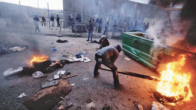 Des manifestants palestiniens brûlent des pneus lors des heurts avec la police, mercredi, dans un quartier arabe de Jérusalem.