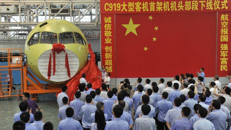 Les techniciens de la Comac dévoilent le nez du C919, à Chengdu, le 31 juillet 2014.