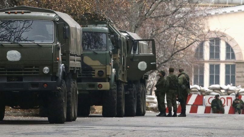 Miliciens et camions militaires des forces pro-russes près d'un checkpoint installé à Donetsk.