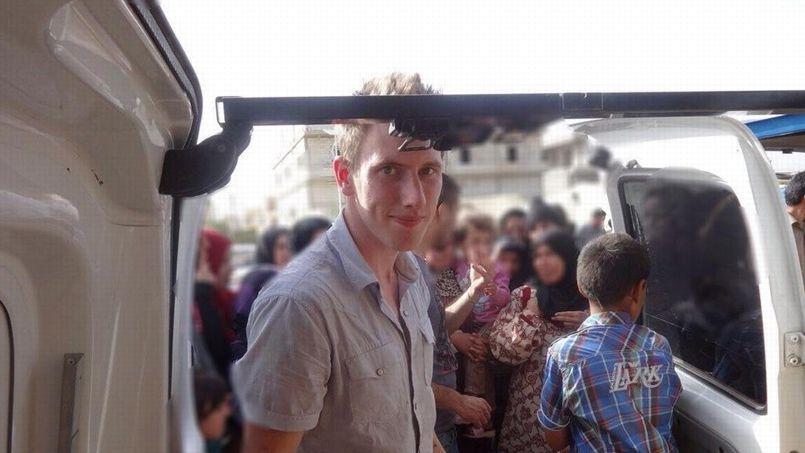 Cette photo montre Peter Kassig devant un camion le long de la frontière syrienne.