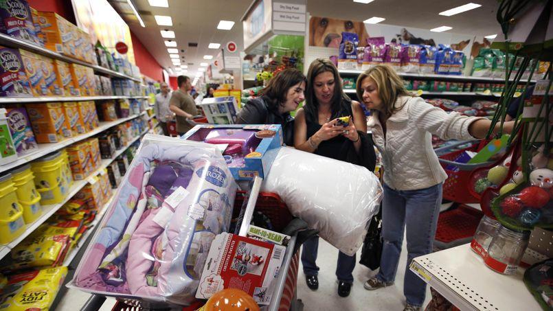 Les consommateurs américains (ici dans un magasin Target à South Portland dans le Maine, jour du Black Friday) regagnent du pouvoir d'achat grâce à la baisse du pétrole.