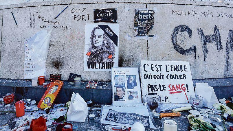 Portrait de Voltaire au milieu des bougies et objets déposés hier en hommage aux personnes assassinées lors des attaques terroristes.