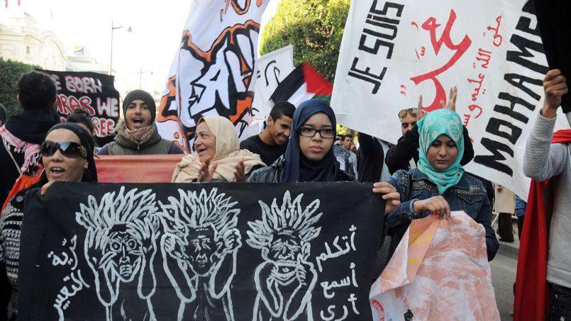 Des protestataires ont défilé en scandant des slogans anti Charlie Hebdo, après la publication du dernier numéro de l'hebdomadaire satirique, mercredi à Tunis. En arrière-plan, l'inscription «Je suis Mahomet» apparaît sur une pancarte.