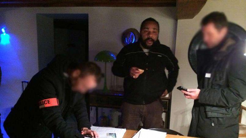 Image diffusée sur le compte Facebook de Dieudonné, le montrant à son domicile entouré de deux policiers.