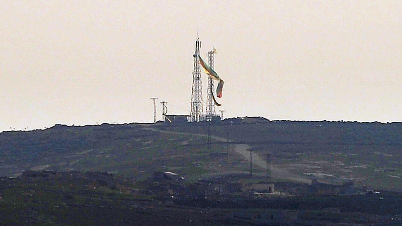 Les combattants des forces du YPG ont symboliquement accroché un drapeau kurde tricolore de 75 mètres de long à un pylône sur une colline surplombant la ville détruite par quatre mois de combats.