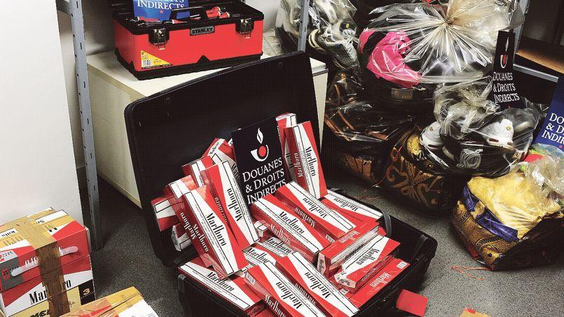 Des cartons de cigarettes et des sacs de vêtements contrefaits, saisis par les douanes, à Orly.