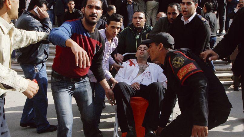 Policiers et passants évacuent une victime de l'attaque terroriste contre la Cour constitutionnelle, lundi 2 mars au Caire.
