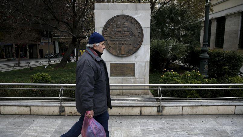 Un homme passe devant une réplique de pièce de drachme, à Athènes.