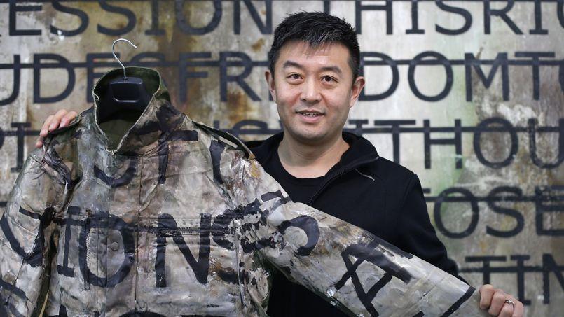 Liu Bolin montre le costume recouvert de peinture qu'il a porté lors du camouflage pour l'œuvre Hiding in the City   Wall.