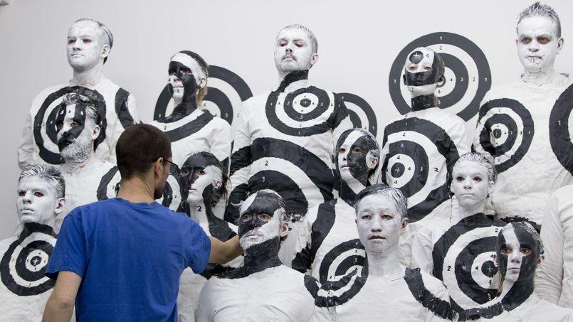 Performance de body painting de Liu Bolin, en collaboration avec Alexis Rero et d'autres artistes, à la Galerie Paris-Beijing à Paris, le 19 mars.