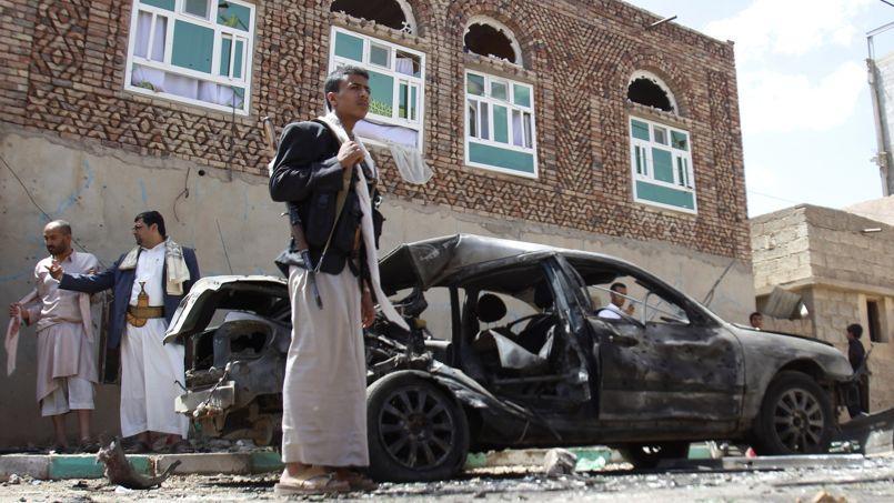 Un milicien Houthi devant une voiture endommagée par l'attaque suicide, le 20 mars 2015 à Sanaa, capitale du Yémen.