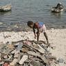 Cette fillette du quartier Martissant essaie de recomposer des paires de sandales trouvées sur le rivage ou en mer, pour ensuite les vendre.
