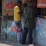 Un mineur fait ses courses avec son fils dans une épicerie d'Ilakaka. Ici 90% des mineurs sont armés.