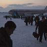 Des passagers d'Air Koryo en provenance de Pékin descendent sur le tarmac enneigé de l'aéroport international de Pyongyang.