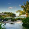 Pose au bord la grande piscine. Au loin, les autres motou de l'atoll.